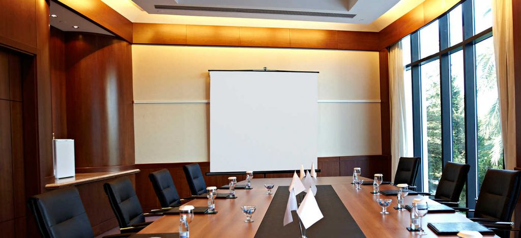 Conference room with a big polished table and arm-chairs